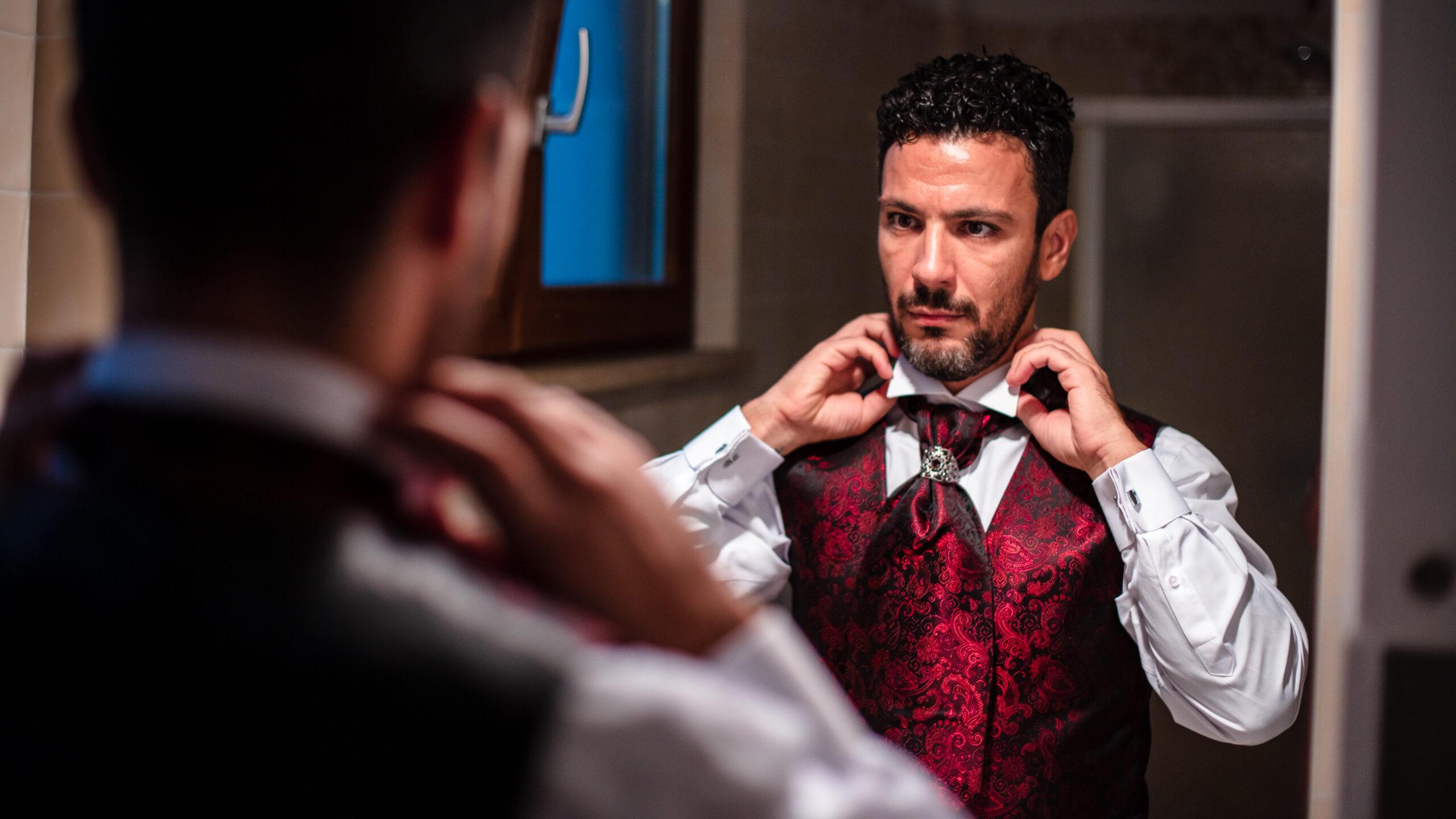 lo sposo aggiusta la camicia allo specchio