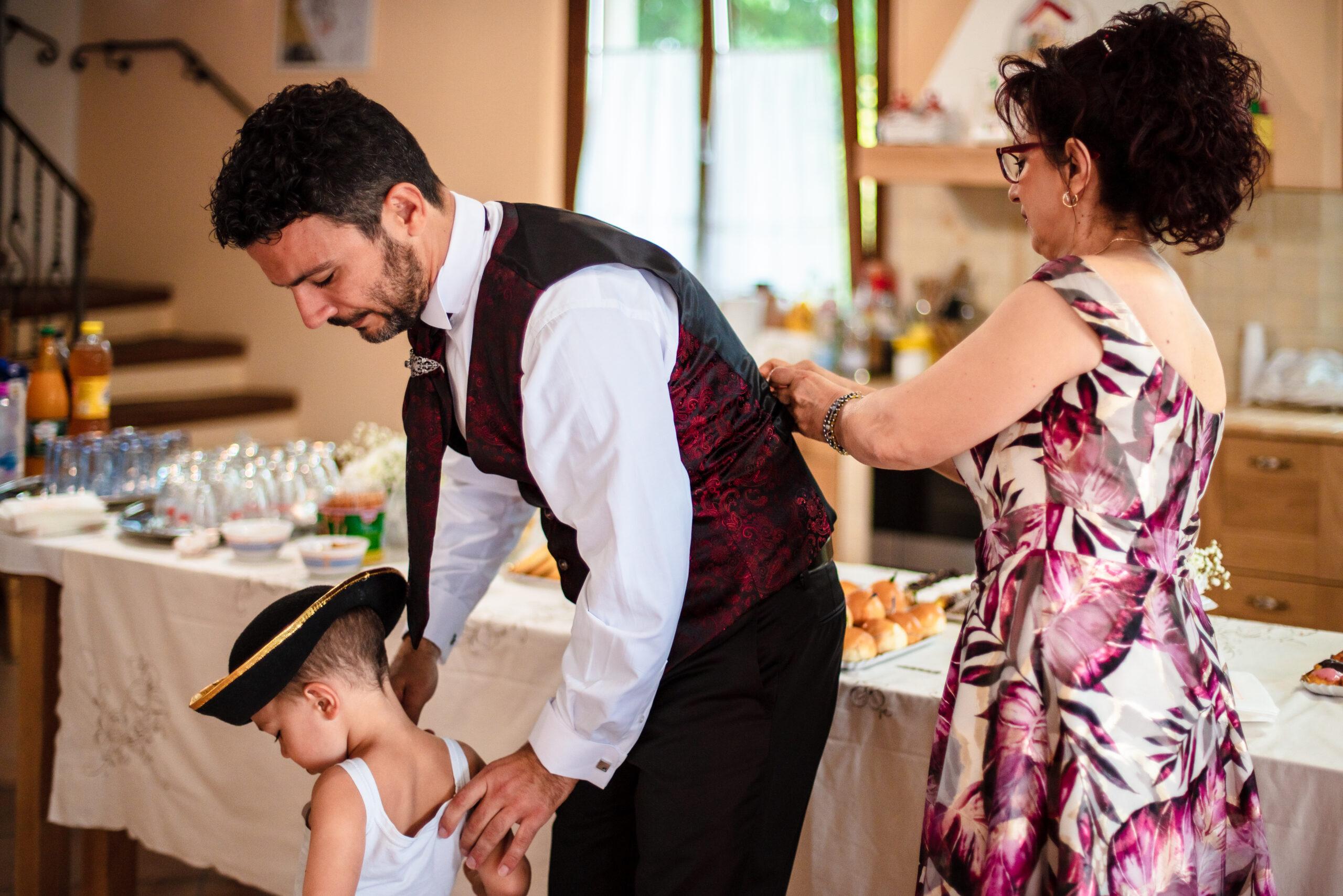 la mamma aggiusta il vestito da sposo