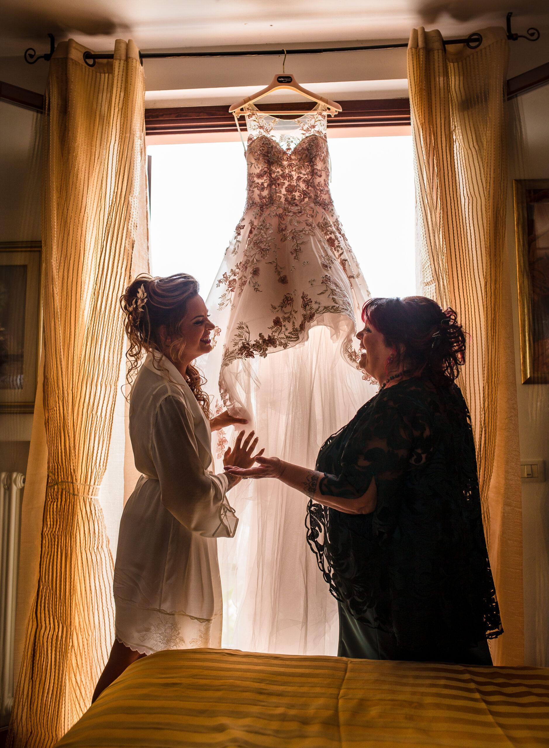 la sposa e la mamma che ridono sotto il vestito da sposa