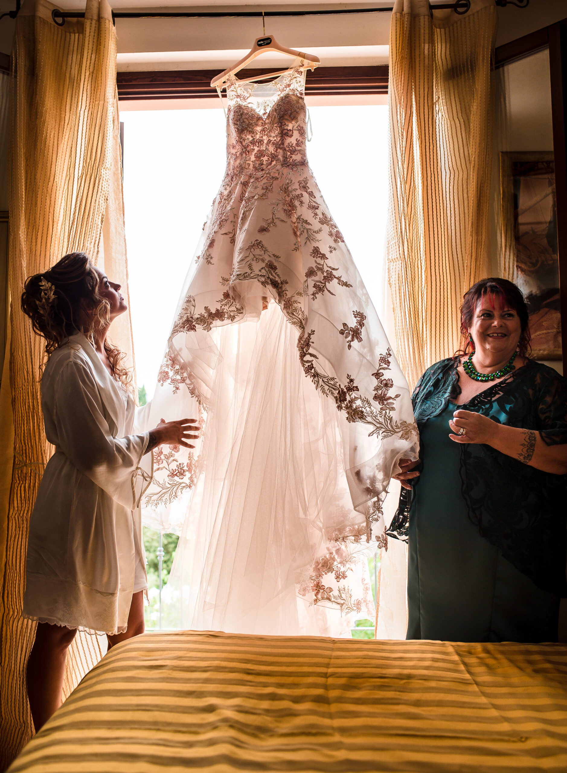 mamma della sposa e la sposa vicino al vestito