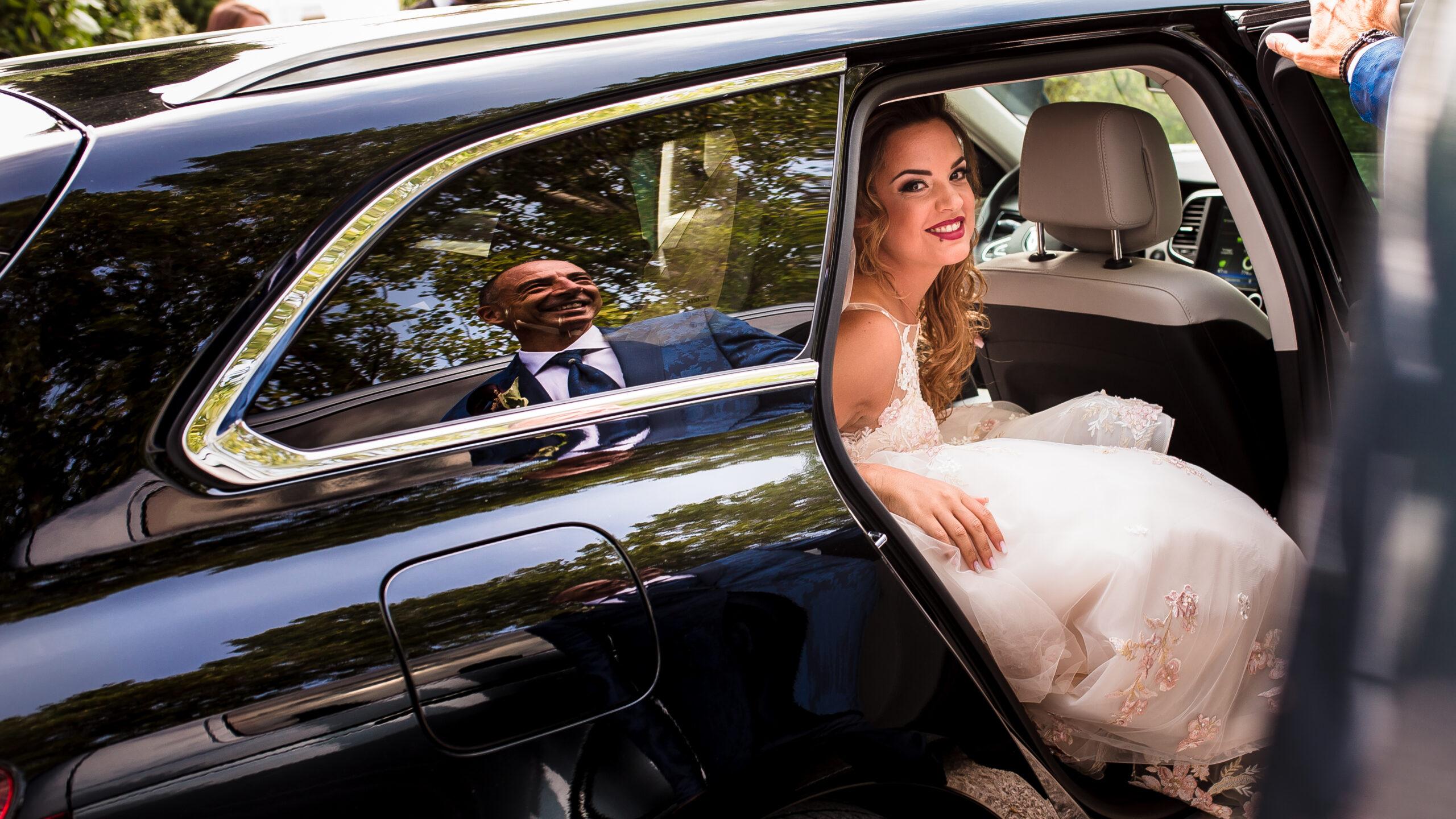 la sposa che scende dalla macchina con il riflesso del papà