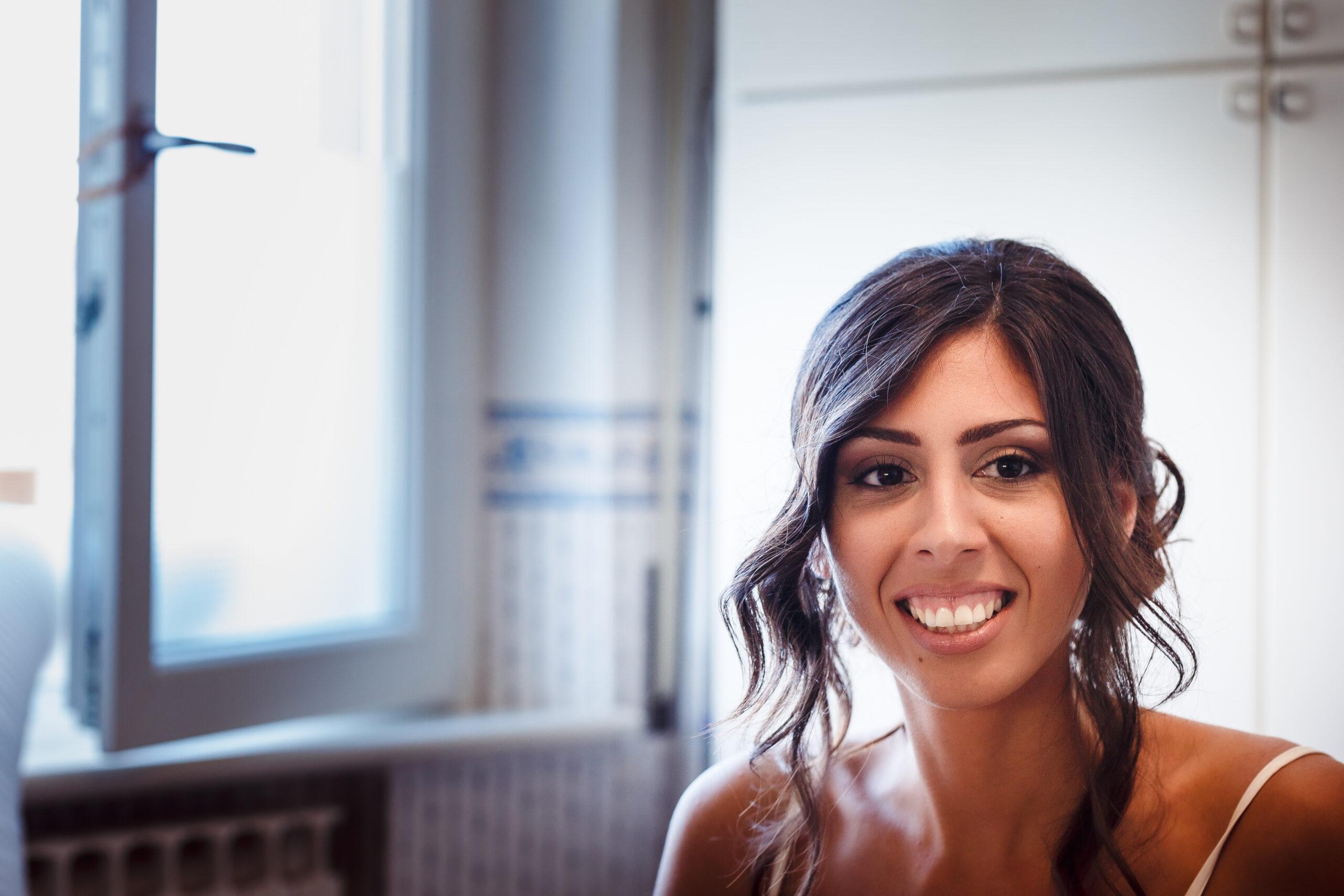 sposa sorridente durante il trucco